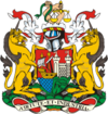 "A coat of arms, with a shield showing a sailing ship and a castle with maned lions on either side, surmounted by the helmet from a suit of arms and two hands holding a snake and scales of justice. The motto at the bottom is ""Virtute et Industria"""