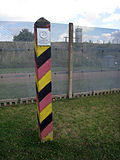 "A square wooden post with diagonal black, red and yellow stripes and a metal sign saying ""DEUTSCHE DEMOKRATISCHE REPUBLIK"" stands in front of a steel mesh fence, through which a guard tower is visible."