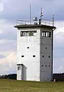 A squat, square white tower on a sloping meadow. Each side of the tower has an unbroken row of windows near the top. There is a searchlight on the tower's flat roof, poles carrying equipment and a railing around the roof's outer edge.