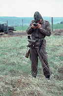 Armed East German guard standing in a grassy field taking a photograph of the photographer. A border fence and a truck are visible in the background, some distance behind the soldier.