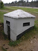 A square white half-buried concrete bunker with a concrete broach roof and rectangular horizontal loopholes. A tall fence is visible in the background.