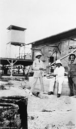 Three men in uniform, two sitting and one standing, outside a number of buildings and earthworks.