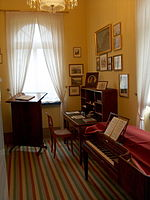 room furnished in early nineteenth century style, with striped runner on floor; walls painted peach and wall on right hung with small pictures; in the right foreground a square piano, in left rear before a window a reading stand, in right rear a desk, all in dark wood