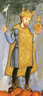 A mediæval illustration of a man with a short red beard wearing a blue tunic and a gold over-tunic, with black tights, holding a golden orb in his left hand and a silver sceptre in his right. Above his red hair, he is wearing a gold crown. Indistinct words are faintly visible above him.