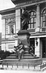 black and white photograph of a statue of a robed male figure on a stepped pedestal, inscribed 'Felix Mendlessohn Bartholdy', with a seated female figure holding a lyre at its base, in front of an arcaded building