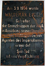 "Damaged metal plaque reading ""Am 3.9.1956 wurde WALDEMAR ESTEL Getreiter der Grenztruppen der NVA in Ausübung seine Dienstes an der Staatsgrenze von Agenten des Imperialismus ermordet. Sein Tod ist uns Verpflichtung."""