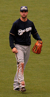 A man wearing a navy blue Brewers jersey, gray pants, navy blue cap, and outfielder's glove on his left hand walking in the outfield.