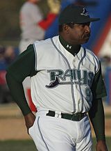 "A man wearing a white baseball uniform with ""Rays"" written across the chest in green and a black cap stands on a baseball field"