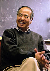 Tsung Dao Lee sitting in a chair, his legs crossed, a blackboard with mathematical equations in the background.