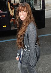 The picture of a woman who is smiling. She is walking on a street and she is looking back over her left shoulder. She wears a grey sweater with some black frames, and jeans of the same colour. In the background a black bus is visible.