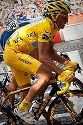 A man in yellow clothes, with a yellow helmet and yellow handgloves, riding a bicycle. Just behind him is another cyclist, in blue clothes.