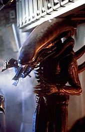 A tall human-like alien creature stands inside the cargo hold of a spacecraft. It is all black in color, has a long, horizontally configured phallic-shaped head with its long rigid tongue extended, long arms with six digits on each hand, and long tubes protruding from its back.