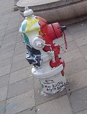 A painted hydrant with vertical stripes of multiple colors