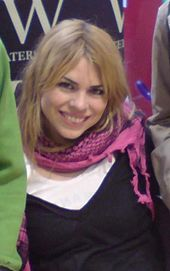 A woman in late 20s with blonde hair and brown eyes, smiling, wearing a white T-shirt, a black tank top and a pink scarf.