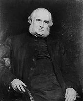 An old man in half-figure on a chair, with his right arm over the back, facing the viewer. His hair and large muttonchops are white, his attire is black and simple.