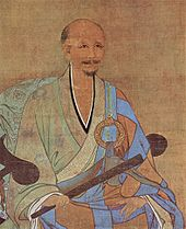A portrait of an older, balding man in a half pale green and half sky blue robe. He is sitting on an armchair holding a thin wooden stick, possibally a folded up fan.