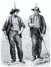 Two men wearing mining attire look at one-another in this black line drawing. Both wear dark clothing and mining helmets. The man on the right holds a long tool.