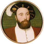 A man with a thick, full beard and a calm expression wearing a doublet jacket and a wide-brimmed hat