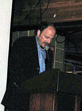 A balding and bearded man stands bowed over a podium.