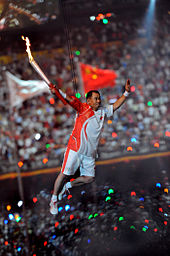 An Asian man in red and white athletic shirt and shorts, and wearing sneakers, is suspended by wires in the air while holding a lit torch. In the background, a large crowd in a stadium can be seen, as well as two blurred flags.