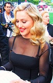 A blond woman in a black dress, smiling and looking down.