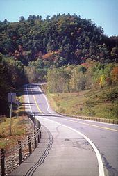 A two-lane highway in a desolate, forested area descends a hill and turns to the right and out of view ahead of a large hill in the background. The road widens to three lanes just ahead of the bend.