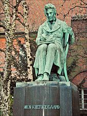 "A statue. The figure is depicted as sitting and writing, with a book on his lap open. Trees and red tiled roof is in background. The statue itself is mostly green, with streaks of grey showing wear and tear. The statue's base is grey and reads ""SØREN KIERKEGAARD"""