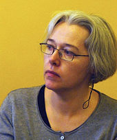Photograph of a woman with short gray hair and glasses.