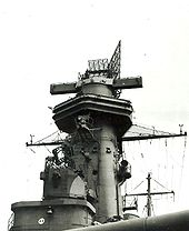 The tower is dominated by a large radar set; two long arms protrude from the side of the tower.