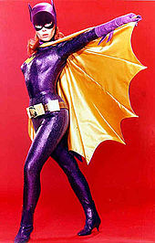 Yvonne Craig poses in the Batgirl costume from the television show, holding the cape open. The costume consists of a purple bodysuit, cowl, gloves, boots, a yellow cape and belt.
