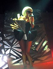 A blond woman standing on a stage. She wears a black tutu shaped dress with a shiny triangle attached on her right bosom. Her hair is in bob and she wears sunglasses while singing to a microphone held in her left hand. Behind her, a set piece encrusted with broken glasses is visible.