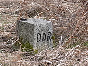 "Square grey stone in scrubby brown grass with ""DDR"" carved on the right face."