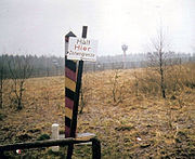 "View across a landscape with a leaning sign reading ""Halt Hier Zonengrenze Bundesgrenzschutz"" in the foreground, a red/black/yellow striped square-shaped pole just behind, and a metal fence and watchtower visible across a strip of open ground in the background."