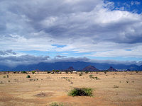 Daytime view of an almost lifeless expanse, dry rocks and sand marked only by the odd lone shrub. The dry terrain reaches to a chain of mountains in the far distance, near the horizon. A bank of clouds soars above the void, but it does not appear to hold the promise of rain. A far darker, larger, more turgid cloud bank sits above the distant mountains, above the horizon.