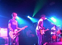Two guitarists and a drummer are performing a song live on a stage lit by blue concert lights