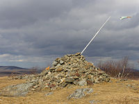 A pile of stones in a grassy clearing in late autumn. A pole with a small windsock protrudes from its right