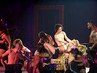 Image of a blond woman. She is laying in a flowered divan, with her body extended and her hands in her head. She is wearing a sparkly bra and lingerie, with black high-heeled shoes. The divan is attached to wires. She is surrounded by several people, including bare chested men of differentes races. Several women also surround her, wearing black lingerie ensembles. Below her, an Hispanic man and an African American woman are touching each other in a sexual way.