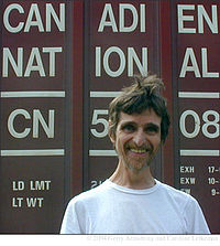 "Head and shoulders photograph of a bearded smiling man in white T-shirt standing in front of a freight car bearing the words ""Canadien National"" and loading information"