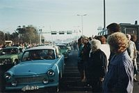East German Trabant cars driving between dense crowds of people. Metal gantries over the road and a watchtower are visible in the background.