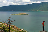 The island of Golem Grad in the dark blue water of Lake Prespa, surrounded by hills and mountains