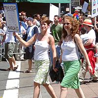 "Photo of two women holding hands, one with short hair and the other with long, both wearing white spaghetti strap blouses that read ""Bride"", and green skirts while the one on the left holds a sign reading ""Married March 11"" with a blown-up reproduction of a marriage license. They are walking down a street with other people walking behind them holding signs as if for a parade or demonstration"