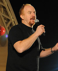 A balding man with red hair and a red goatee, wearing a black T-shirt, speaks into a microphone.