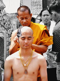 A Buddhist monk shaving the head of a devotee to prepare him for priesthood.
