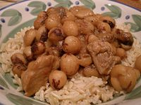 Closeup of large round speckled beans cooked with cubes of pork over rice