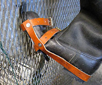 Close-up view of a boot which has been modified with a hooked overshoe, shown on a section of border fence to demonstrate how it would have been used to climb it.