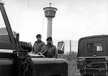 "Two British soldiers carrying rifles standing behind a pair of Land-Rover vehicles, one of which has a ""British Frontier Service"" plate. Behind them is a high mesh fence, behind which is a tall watchtower with an octagonal cabin at its top."