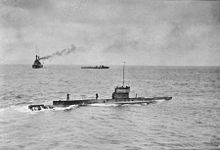 A submarine moves across the surface of the ocean, while two warships can be seen in the background