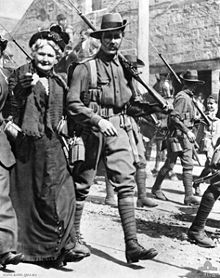 Troops marching through a city street lined with a crowd of people. In the foreground is a soldier and beside him is an older women.