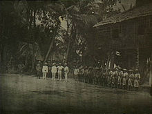 A line of soldiers in tropical uniforms stand in front of a hut in a jungle clearing. In front of them stand a group of five men facing towards the camera