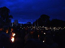 People gather with candles in the dim light of dawn in front of a large stone building and a line of flag poles